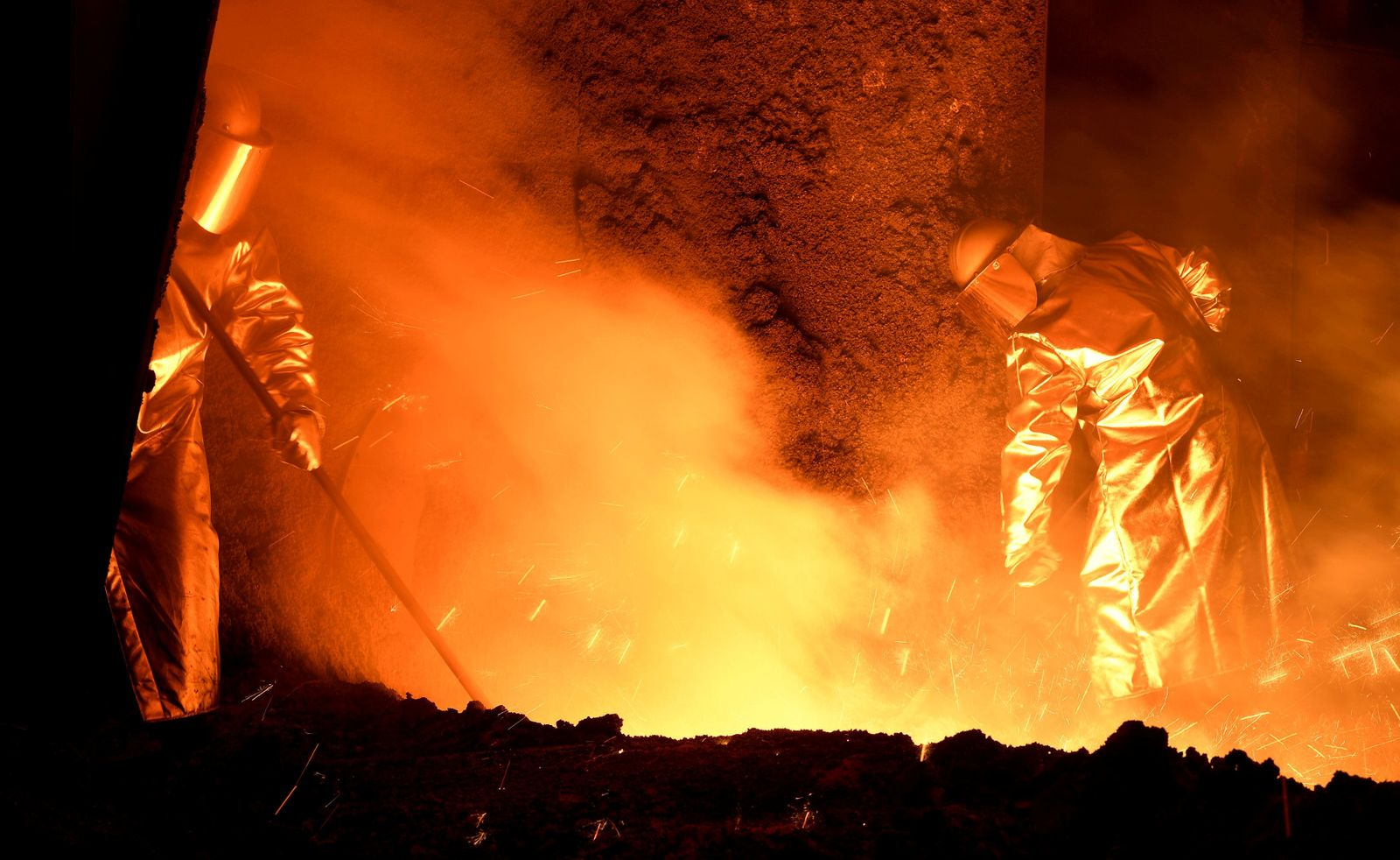 FILE PHOTO: Steelworkers stand at a furnace at the plant of German steel company Salzgitter AG in Salzgitter
