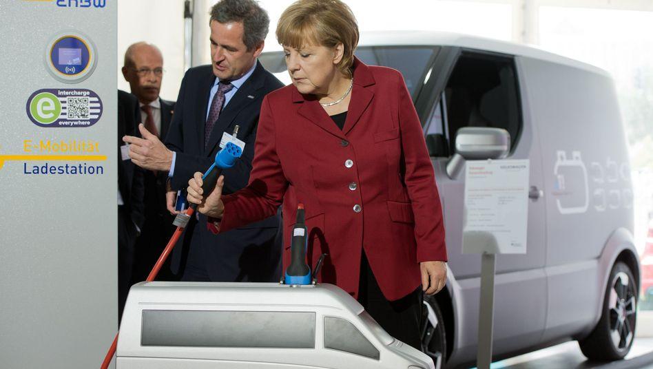 Kanzlerin Angela Merkel vor einer Ladestation: Die Regierung drängt darauf, die Ladestecker europaweit zu vereinheitlichen