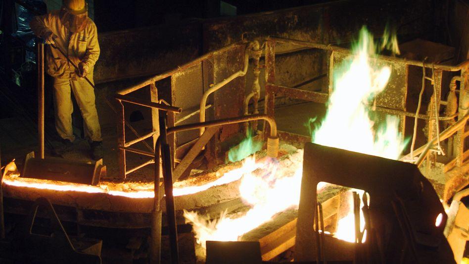 Alles im Blick: Ein Arbeiter bearbeitet flüssiges Kupfer auf dem Gelände der Aurubis AG in Hamburg