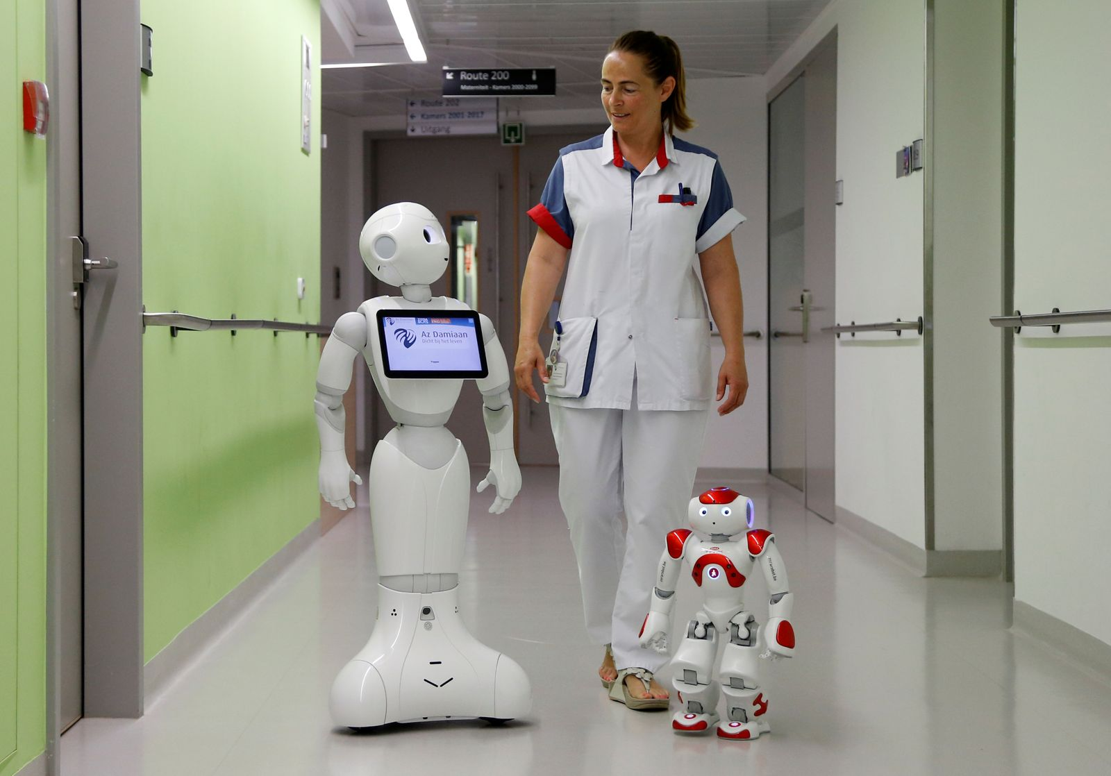 "A nurse walks with ""Pepper"" and ""Zora"" the robots, humanoid robots designed to welcome and take care of visitors and patients, at AZ Damiaan hospital in Ostend"