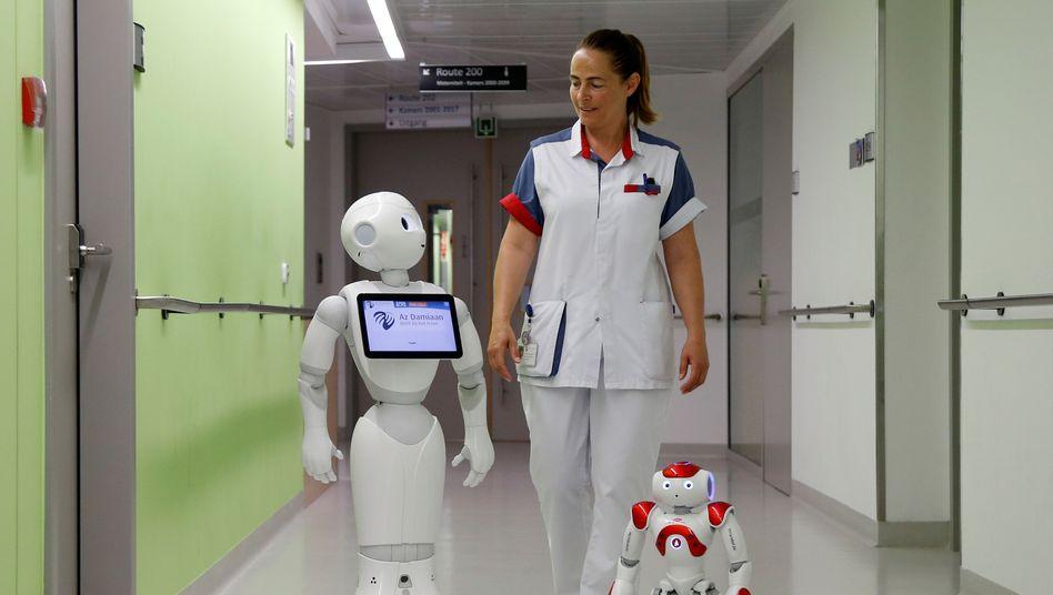 """Pflegeroboter: Eine Krankenschwester in Belgien wird von den Robotern """"Pepper"""" und """"Zora"""" begleitet."""