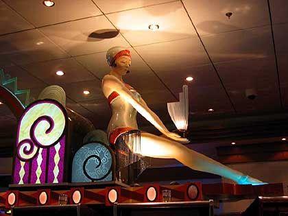 Automaten-Casino: Auf den einarmigen Banditen räkeln sich Frauenskulpturen im Charleston-Kostüm