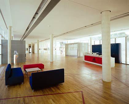 Bitte eintreten: Die längliche Eingangshalle besticht mit Sitzgruppen in poppigen Farben, schlichten Säulen und schickem Holzfußboden. Einzelne Turnschuhmodelle von Adidas-Salomon werden wie Kunstobjekte ausgestellt.