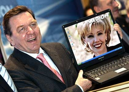 Unterwegs im Namen der Messe: Bundeskanzler Gerhard Schröder zeigt ein Laptop mit Porträt der Gattin