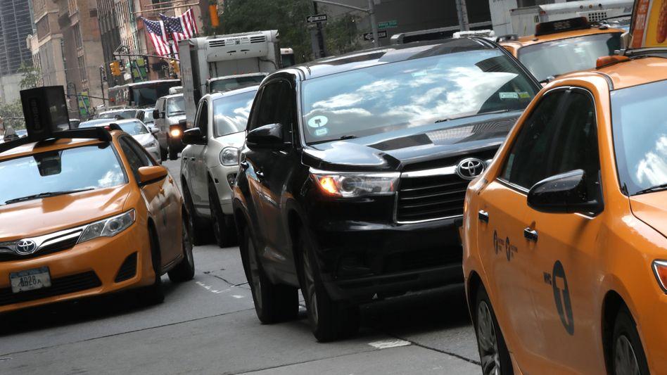 Uber und Taxifahrzeuge in New York: Weil viele Fahrer weniger als den Mindestlohn verdienen, verschärft die US-Metropole nun die Regeln für die Fahrdienstvermittler