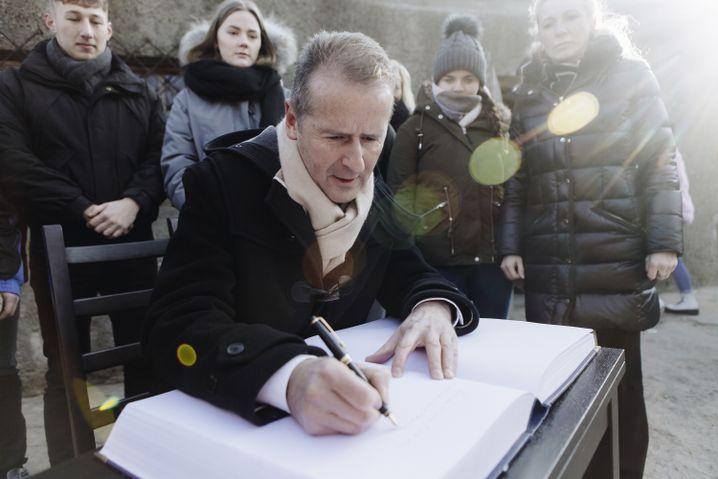 VW-Chef Diess trägt sich im November 2018 in das Besucherbuch der Gedenkstätte Auschwitz ein.