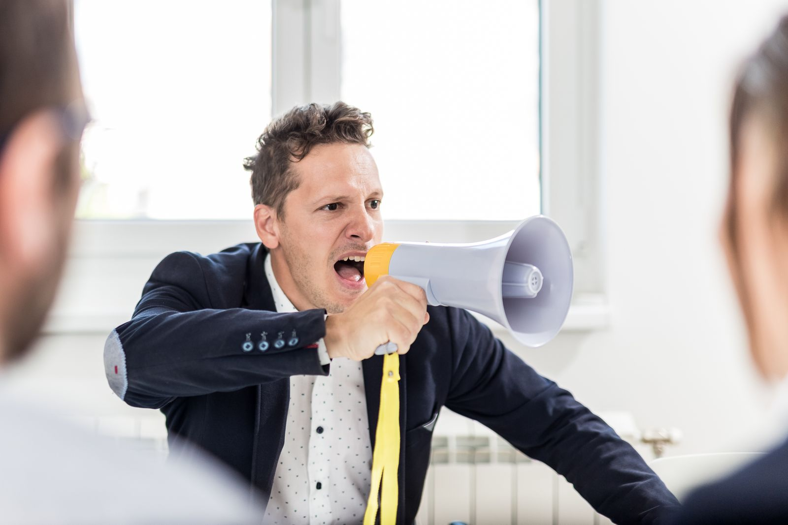 Young boss shouting at employees through megaphone in conference room.