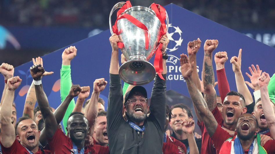 Jürgen Klopp (mit Brille) stemmt inmitten seiner Spieler den Champions-League-Pokal in die Höhe