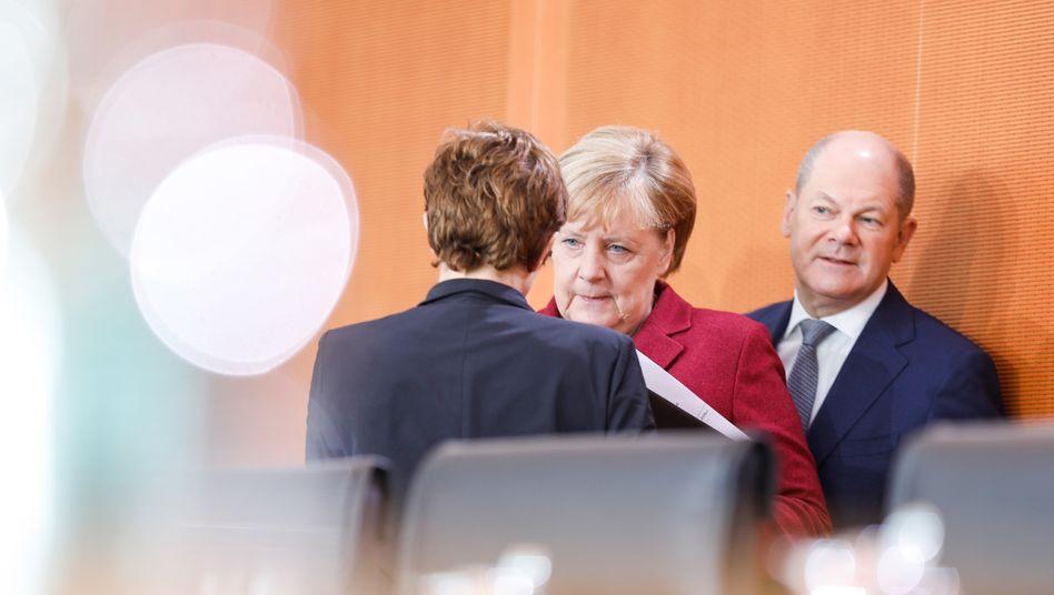 Finanzminister Scholz mit Kanzlerin Angela Merkel und Verteidigungsministerin Kramp-Karrenbauer (von hinten)